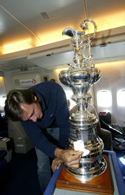 03_2203D ©Th.Martinez - Airplane (Auckland to Geneva) . America's Cup 2003. 8th March 2003.Alinghi Team winner of America's Cup 2003..Alinghi's president and navigator Ernesto Bertarelli, cleaning THE CUP  in the plane to Geneva....