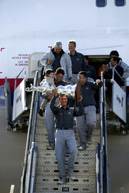 03_2209D ©Th.Martinez Team .Geneva , Switzerland. America's Cup 2003. 8th March 2003.Alinghi Team winner of America's Cup 2003, arriving in Geneva Airport with thE America's Cup. Alinghi 's President and navigator holding the America's Cup, and folowed bt Russell Coutts (with his son Michael) and Michel Bonnefous, Brad Butterworth and Jochen Schuemann.They are arriving in Geneva airport by a specia lplane from Auckland. First time since the first Regatta in 1851 that the America's Cup is going back to Europe....